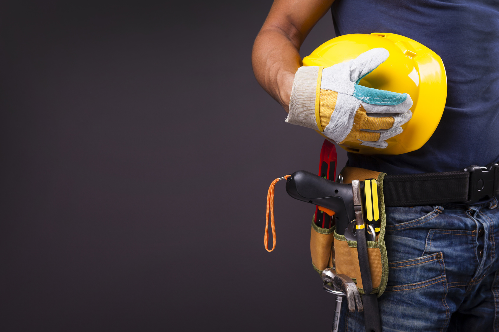 Up-close view of a man's utility belt and hardhat in his hands.